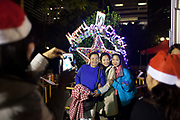 A group of Filipino women take photographs of each others with a Christmas decoration. It is Christmas Eve and thousands of Catholic Filipino women have congregated in Central Hong Kong to celebrate Christmas. Hong Kong has a huge Filipino population, most of them women working as domestic servants. They meet in public on their days off since none of them have their own private accomodation. 7 million people live on 1,104km square, making it Hong Kong the most vertical city in the world.