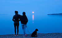Girls watch the full moon rise over the ocean at Cordova Bay, in Victoria, BC.