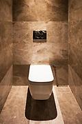 Detail of toilet in a marble bathroom. Nobody inside