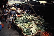 A child leans against an adult shopping for fresh vegetables at an Aberdeen street market, on 16th April 1979, in Hong Kong, while still UK.