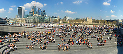 © Licensed to London News Pictures. 20/04/2018. London, UK. An i-Phone panorama of crowds of office workers and tourists sit in the sunshine on the south bank of the River Thames in front of City of London skyscrapers and the Tower of London. Photo credit: Vickie Flores/LNP