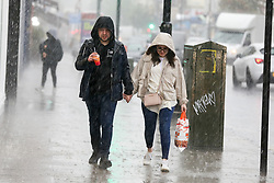 © Licensed to London News Pictures. 17/05/2021. London, UK. A couple are caught in heavy rain in north London. More rain is forecast for the South East of England this week. Photo credit: Dinendra Haria/LNP