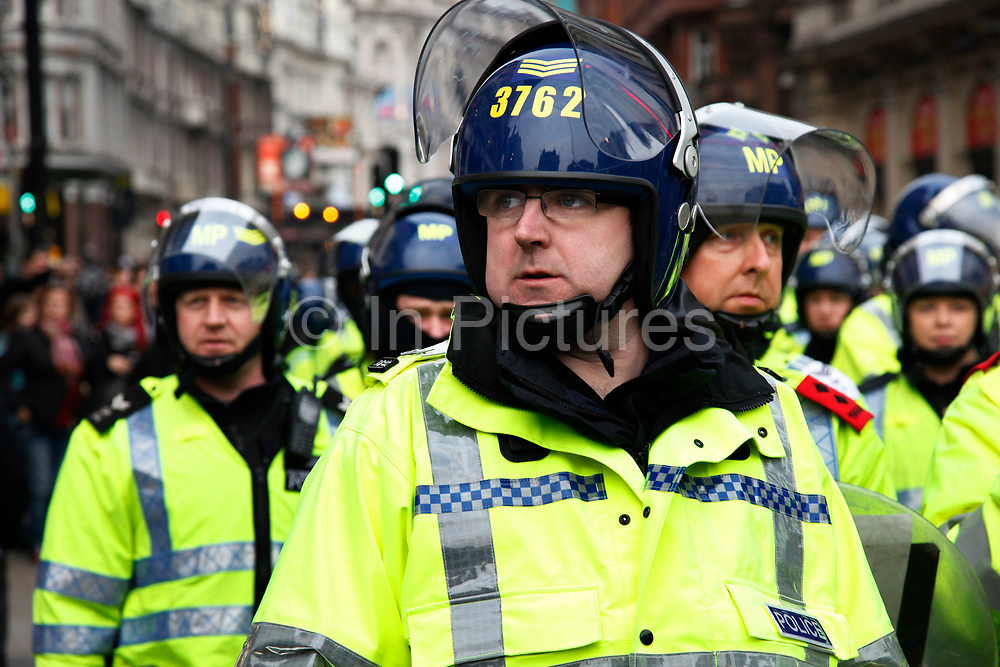 Riot police wait and assess the area near Piccadilly Circus. Anti capitalists / anarchists go on the rampage through central London on the back of the peaceful TUC protest march. The masked demonstrators ran a twisting route through the capital confusing the police and creating a situation which was very difficult to manage. The protesters attacked banks, shops and hotels, and the police in riot gear fought  face to face with them as they were pelted with ammonia, paint and fireworks loaded with coins.