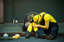 © Licensed to London News Pictures . 31/10/2015 . Manchester , UK . A woman and man , dressed up as Minions , sit together slouched over in the gutter . Halloween revellers , wearing make up and costumes , out and about in Manchester City Centre . Photo credit : Joel Goodman/LNP