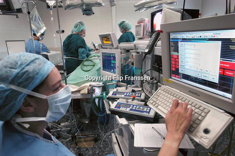 Nederland, Nijmegen, 9-1-2015Operatie in een operatiekamer van een ziekenhuis. Een anesthesist is aan het werk met computergestuurde bediening van de apparatuur.Foto: Flip Franssen