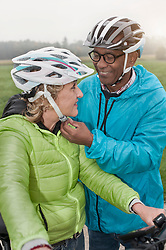 Senior man fastening on bicycle helmet to his wife and smiling, Bavaria, Germany