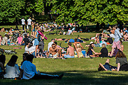 Large groups relax and meet, against guidance, in St James Park as the sun comes out again. The 'lockdown' continues for the Coronavirus (Covid 19) outbreak in London.