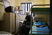 An elderly prisoner reading the newspaper in his cell, HMP & YOI Littlehey. Littlehey is a purpose build category C prison.