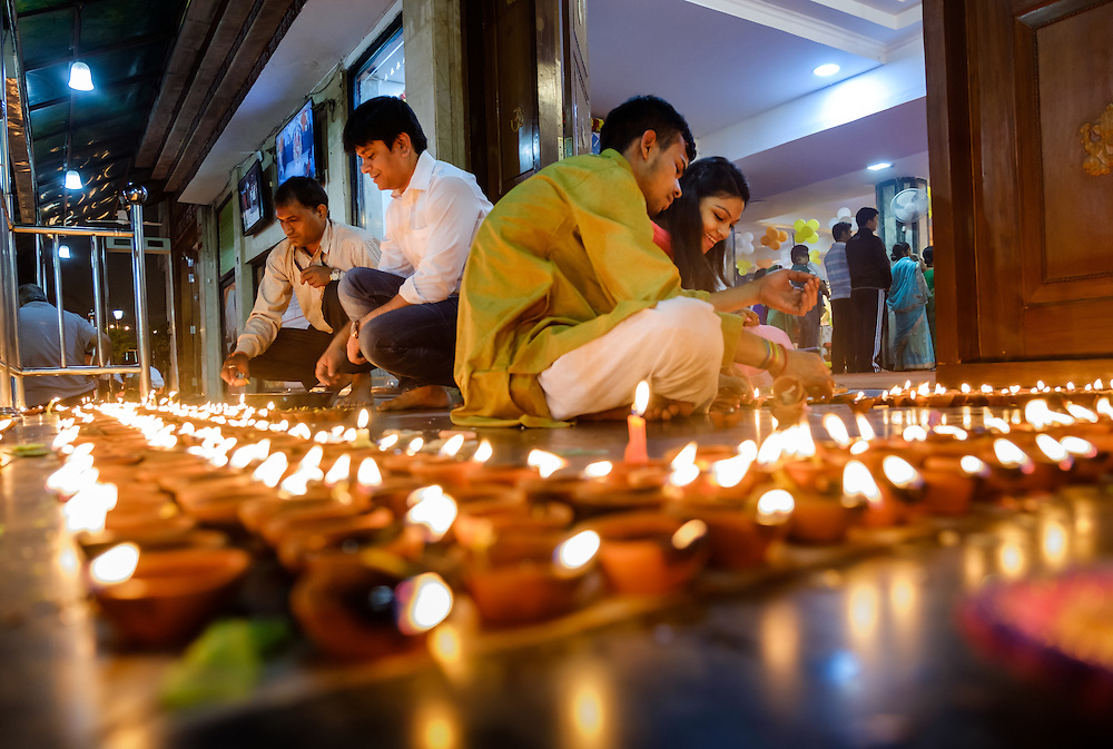 NEW DELHI, INDIA - CIRCA OCTOBER 2016: People lighting candles for the Diwali celebration at the Sai Baba Temple in the Hauz Khas area of New Delhi. Diwali is also known as festival of lights, for the Hinduism, it spiritually signifies the victory of light over darkness, good over evil, knowledge over ignorance, and hope over despair. Its celebration includes millions of lights shining on housetops, outside doors and windows, around temples and other buildings in the communities.