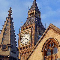 United Kingdom, Great Britain; England; London. Famous Big Ben clocktower snugled between a spire and a rooftop representing three types of architecture.