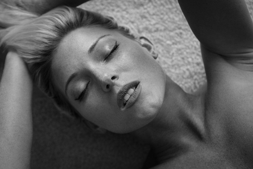 Black and white close up of a woman's face with arms above head while she is laying on a carpet
