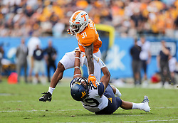Sep 1, 2018; Charlotte, NC, USA; Tennessee Volunteers running back Madre London (31) breaks a tackle from West Virginia Mountaineers cornerback Sean Mahone (29) during the first quarter at Bank of America Stadium. Mandatory Credit: Ben Queen-USA TODAY Sports