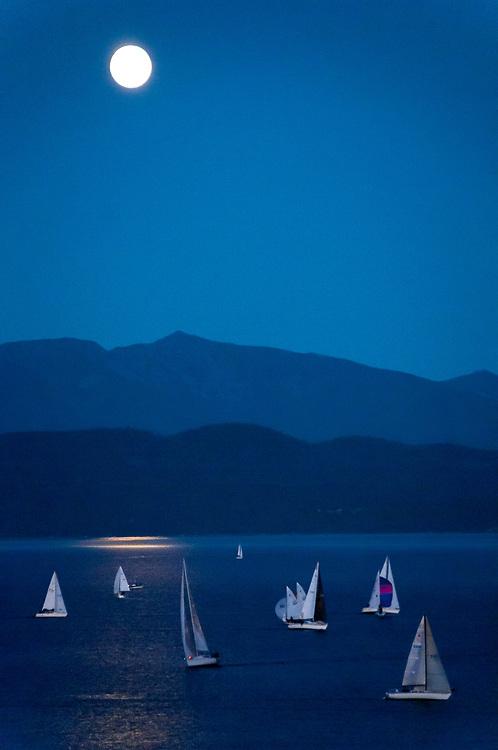 Sailboats on Flathead Lake at night under a full moon with Swan Range visible