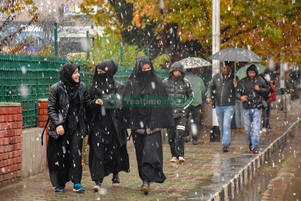 November 3, 2018 - Srinagar, Jammu & Kashmir, India - Kashmiri Muslims are seen walking during the season's first snow fall. Snowfall in the Indian parts of Kashmir has disrupted power supply, air traffic, and road traffic between Srinagar and Jammu, the summer and winter capitals of India's Jammu-Kashmir state, according to news reports. (Credit Image: © Idrees Abbas/SOPA Images via ZUMA Wire)