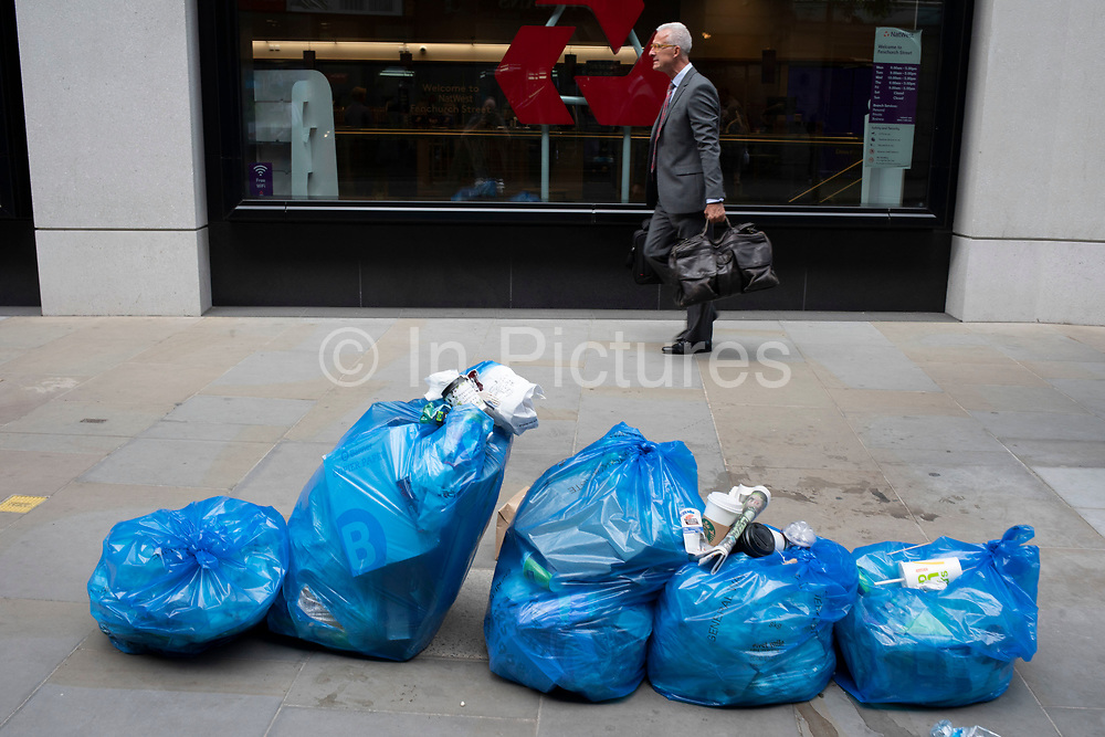 Blue general waste rubbish bags on Fenchurch Street in the City of London, England, United Kingdom. Collection of recyclable waste is the city is important business, while doesnt always make the streets look clean.