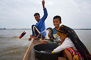 FISHERMEN MEKONG RIVER. South East Asia, Cambodia, Phnom Penh, Mekong River. The Cham fisher people live in various desolated villages along the banks of the Mekong and Tonle Sap rivers. The fisher families live like river gypsy nomads, working and living on their boats, sleeping under a sprung bamboo frame, all their worldly goods stored below deck. They live in extended families, with numerous boats, together for safety. Their diet is rice, vegetables and fish. Their sleek wooden boats are powered by petrol outboard motors with batteries or generators to supply lighting at night. Their fishing technique is laying nets twice or three times per day, which are weighted well below the surface, using old paint aerosal canisters as buoyant floaters, hanging just beneath the surface. These particular fisher families, living at the junction of the Mekong and Tonle Sap rivers, overlooked by Phnom Penh, sell their catch at the Vietnamese market, on the banks of the river. Their life and fortunes are controlled by the cycle of the river. As the river levels drop, so the quantity of fish decreases, until after the heavy floods of the monsoon they fill the river again. They are poor traditional Muslims, marginalised from mainstream society, living a third world life in the immmediate shadow of the first world. The Cham, originally a people of an ancient kingdom called Champa, are a small and disenfranchised community who were disinherited of their land. They are a socially important ethnic group in Cambodia, numbering close to 300,000. The Cham people, live in some 400 villages across Kampong Chnang and Kampong Cham provinces. Their religion is Muslim and their language belongs to the Malayo-Polynesian family. Their livelihoods are as diverse as rice farming, cattle trading, hunting and fishing.///Sok Ray, 34 year old fisherman, with his son Sary and his daughter Asimas, fishing on the Mekong river