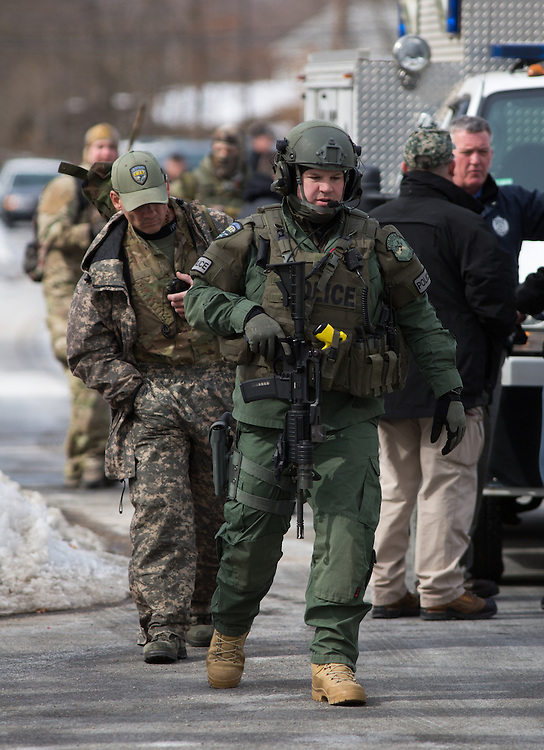 Dedham, MA 03/07/2014<br /> Metro SWAT officers gather on Sherwood St in East Dedham after reports of a man barricaded in a home on Leonard St on Friday afternoon.<br /> Alex Jones / www.alexjonesphoto.com