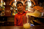 A Nepalese teenage boy pours a drink into a glass at the bar in the Third Eye Restaurant, in the tourist are of Thamel, Kathmandu, Nepal.  He is 18-years old and has done three months training to become a bar tender.  He won a scholarship to do the training with Friends of Needy Children organization.  He belongs to a very poor family who live in a village 2 hours drive from Kathmandu.