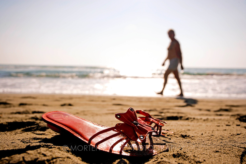 Sandal in sand on beach, man walking in behind