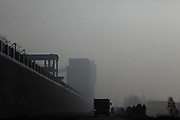 A truck and a motorcycle are barely visible through the thick haze near a coking factory in Linfen, Shanxi Province, China on Thursday, 03 December, 2009.  Due to the heavy presence of coal mines and related industries, Linfen was named the world's most polluted city from 2004-2007.