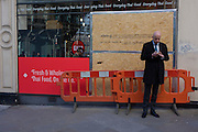 A businessman checks his messages in front of a partially-boarded up Thai food restaurant in the City of London.