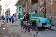 Cuban man of mixed race riding a bike down a dilapidated street in Havana old town, with a car undergoing maintainence in the background and a family walking.