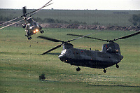 Two RAF CH-47 chinooks soar through the open plains of a British military training area after dropping troops of the Parachute Regiment onto exercise. Famous for their distinctive 'woka' sound and extraordinary lift capability they have become the soldiers' favourite taxi. Photograph by Terry Fincher May 1990.
