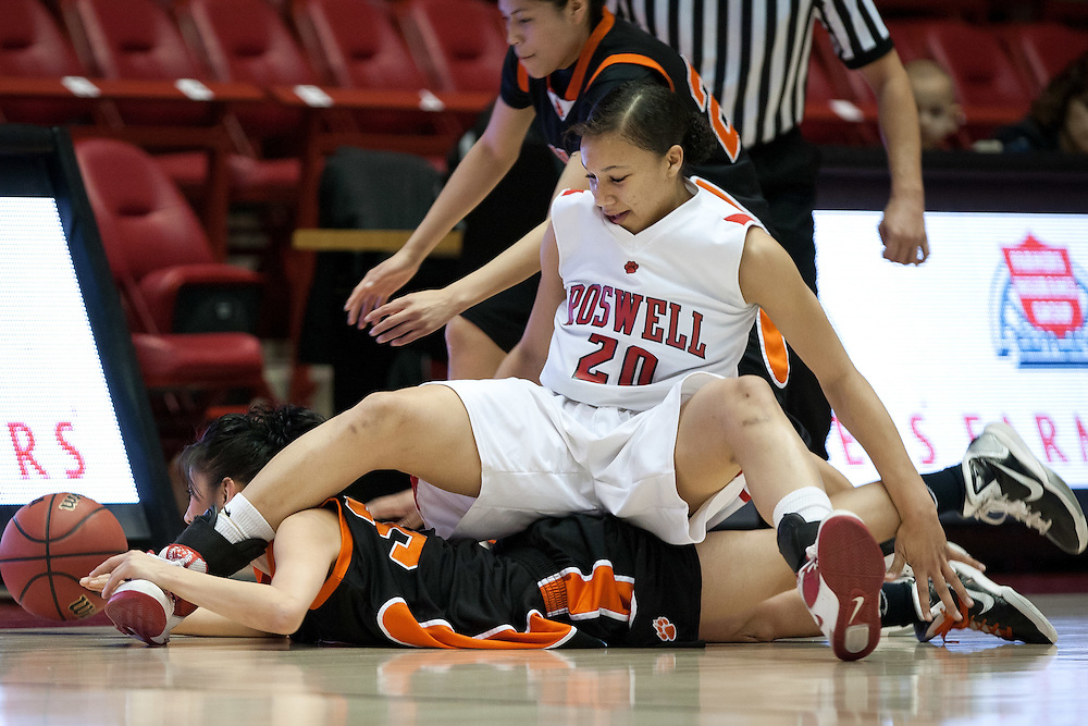 Gallup's Celia Herrera crashes under the legs of Roswell's Shanice Steenholdt while chasing a loose ball. Gallup defeated Roswell 50-44 in the AAAA semifinals Thursday morning in Albuquerque at The Pit.