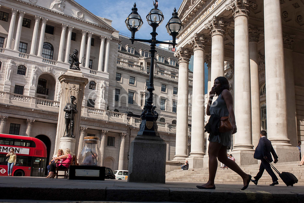 Londoners sit in and walk through Bank Triangle, with the Bank of England on the left and Royal Exchange on the right, on 24th August 2016, in the City of London, UK. The pillars with Corinthian capitals at the top show a neo-Roman style of these banking and financial institutions in the capitals financial district, founded by the Romans in the first Century.