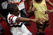 Darious Bryan, 10, member of the Hip Hop Church Choir, is dancing during a Mass Service at the Hip Hop Church in Harlem, New York, NY., on Thursday, June 22, 2006. A new growing phenomenon in the United States, and in particular in its most multiethnic city, New York, the Hip Hop Church is the meeting point between Hip Hop and Christianity, a place where ëGodí is worshipped not according to religious dogmatisms and rules, but where the ëHoly Spirití is celebrated by the community through young, unique, passionate Hip Hop lyrics. Its mission is to present the Christian Gospel in a setting that appeals to both, those individuals who are confessed Christians, as well as those who are not regularly attending traditional Services, while helping many youngsters from underprivileged neighbourhoods to feel part of a community, to make them feel loved and to help them not to give up when problems arise. The Hip Hop Church is not only forward-thinking but it also has an important impact where life at times can be difficult and deceiving, and where young people can be easily influenced for the worst purposes. At the Hip Hop Church, members are encouraged to sing, dance and express themselves in any way that the ëSpirit of Godí moves them. Honours to students who have overcome adversity, community leaders, church leaders and some of the unsung pioneers of Hip Hop are common at this Church. Here, Hip Hop is the culture, while Jesus is the centre. Services are being mainly in Harlem, where many African Americans live; although the Hip Hop Church is not exclusive and people from any ethnic group are happily accepted and involved with as much enthusiasm. Rev. Ferguson, one of its pioneer founders, has developed ëHip-Hop Homileticsí, a preaching and worship technique designed to reach the children in their language and highlight their sensibilities, while bringing forth Christianity. This ëKeep It Realí evangelism style is the centrepiece of Rev. Fergusonís ministry, one that speaks