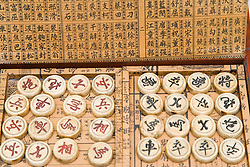 Box of Chinese chess pieces; with proverbs written on the inside of the lid,