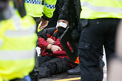 Colnbrook, UK. 27th September, 2021. Metropolitan Police officers arrest an Insulate Britain climate activist who had glued himself to a slip road from the M25 at Junction 14 close to Heathrow airport as part of a campaign intended to push the UK government to make significant legislative change to start lowering emissions. The activists are demanding that the government immediately promises both to fully fund and ensure the insulation of all social housing in Britain by 2025 and to produce within four months a legally binding national plan to fully fund and ensure the full low-energy and low-carbon whole-house retrofit, with no externalised costs, of all homes in Britain by 2030.