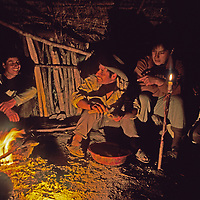 Peruvian arrieros (mule drivers) laugh around a campfire as they camp on the trail while working with a National Geographic archaeology expedition to the Cordillera Vilcabamba mountains in the Andes.