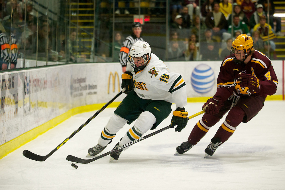 Catamounts forward Matt White (19) battles for the puck with Gophers defensemen Seth Helgeson (4) during the men's hockey game between the Minnesota Golden Gophers and the Vermont Catamounts at Gutterson Field House on Friday night November 23, 2012 in Burlington, Vermont.