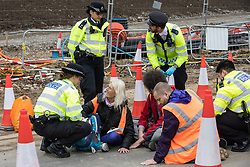 Insulate Britain climate activists are pictured glued onto a slip road from the M25 at Junction 25 as part of a campaign intended to push the UK government to make significant legislative change to start lowering emissions on 15th September 2021 in Enfield, United Kingdom. The activists, who wrote to Prime Minister Boris Johnson on 13th August, are demanding that the government immediately promises both to fully fund and ensure the insulation of all social housing in Britain by 2025 and to produce within four months a legally binding national plan to fully fund and ensure the full low-energy and low-carbon whole-house retrofit, with no externalised costs, of all homes in Britain by 2030 as part of a just transition to full decarbonisation of all parts of society and the economy.