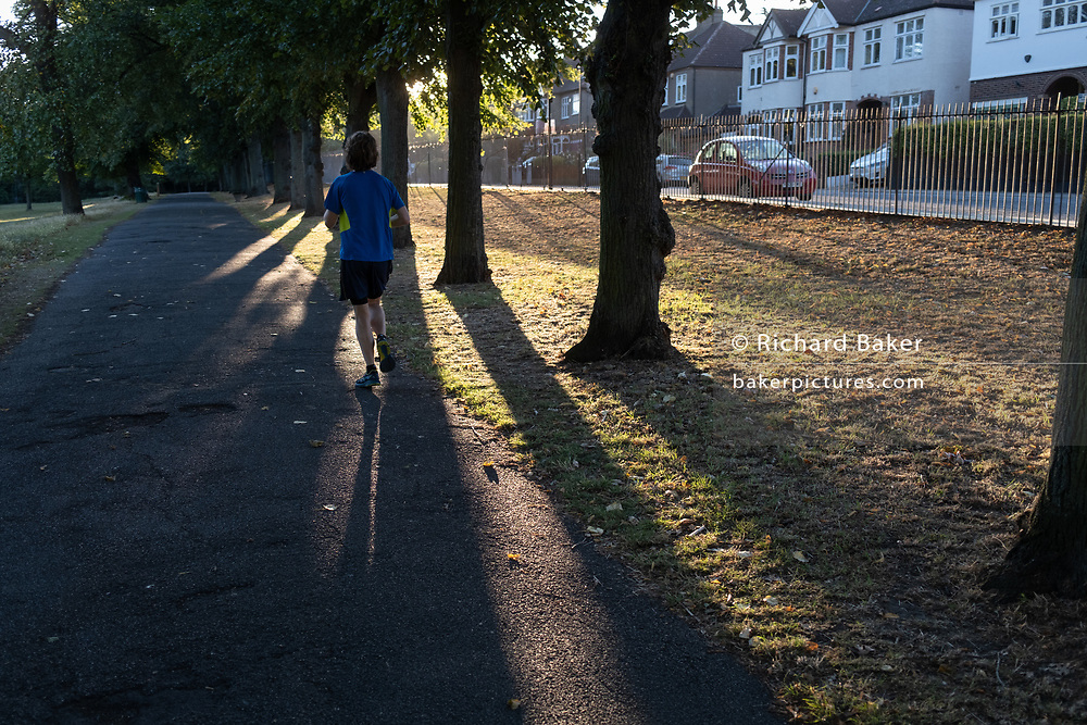 An early runner passes between trees in summer sunlight in Ruskin Park, on 30th July 2020, in Lambeth, south London, England.