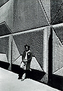 Youth standing against patterned concrete wall. Photo by Richard Saunders 1983