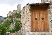 View up to the hilltop tower fortress. A wooden door. Pocitelj historic Muslim and Christian village near Mostar. Federation Bosne i Hercegovine. Bosnia Herzegovina, Europe.