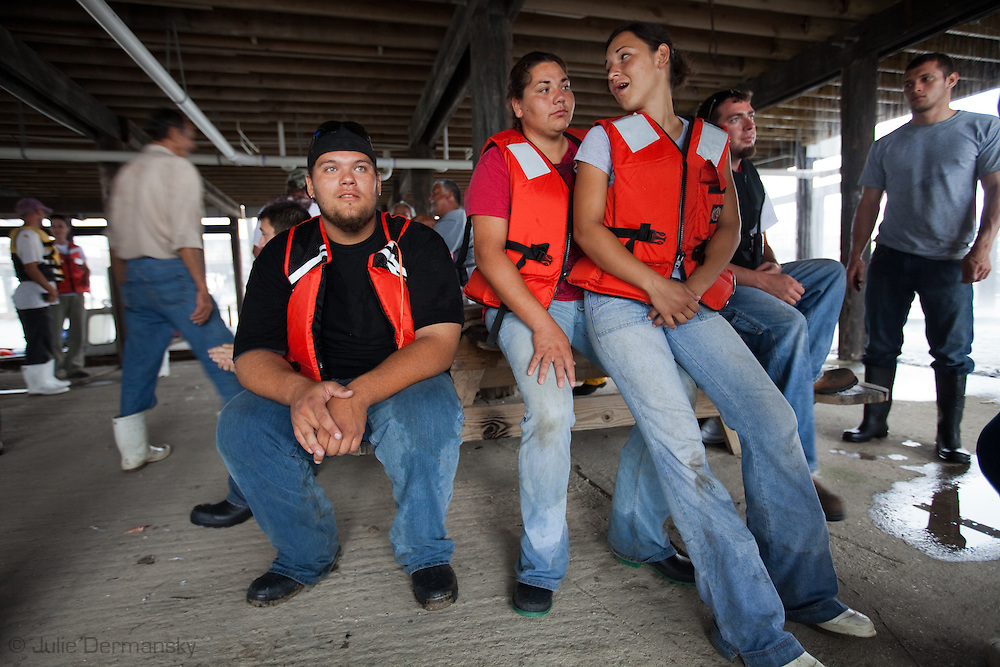 Grace Welch with  her cousin Tracie Verdin and  Josh Bergeron and all Pointe-au-Chien Indians living in Pointe aux Chene have been  shrimpers their   whole lives. They signed on to work for BP  putting out boom out  since no other work is available . The first day on the job, all the boats were called back due to inclement weather. All the workers who singed on to work for BP gather under a raised building at  Point-aux-Chene's boat launch waiting for the rain to let up.