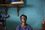 Adjua Yao, 45, who is HIV positive, sits in a room of her sister's home in the Campement neighborhood of Abidjan, Cote d'Ivoire on Wednesday July 10, 2013. Adjua, a mother of five, is currently unemployed and lives with her sister. She's under ARV treatment and takes three pills a day.