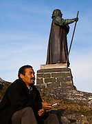 Man sits beside the statue of Hans Edege, Nuuk, Greenland, a Danish-Norwegian missionary who arrived in 1721 and founded the city  - then known as Godthab - in 1728.