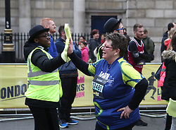 A volunteer high fives a runner after they cross the finish line of the 2018 London Landmarks Half Marathon. PRESS ASSOCIATION Photo. Picture date: Sunday March 25, 2018. Photo credit should read: John Walton/PA Wire