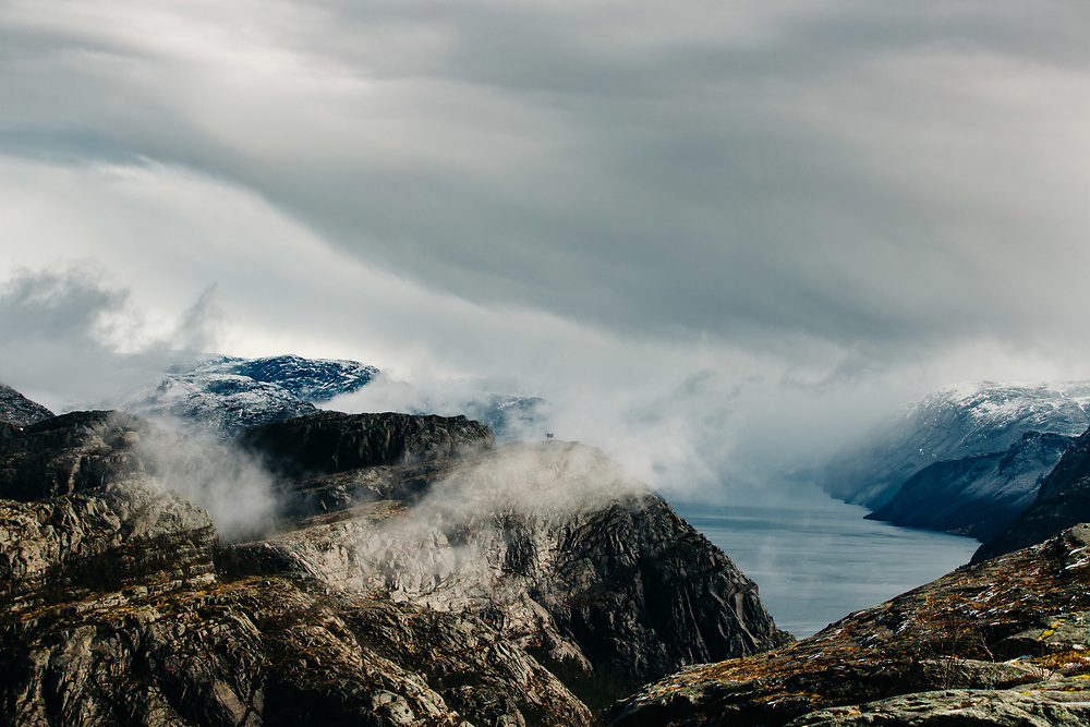 Clouds shroud the mountains surrounding Lysefjorden in Norway