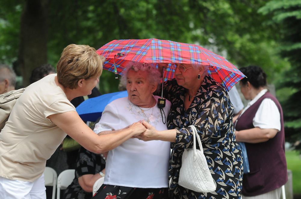 Lucjana Wilczewska (r to l) and Anna Wolkowska are greeted with a sign of peace from a fellow attendee of a Memorial Day Field Mass celebrated at St. Adalbert Cemetery in Niles.