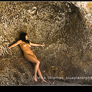 Nude woman posed standing along a curved rock wall with painted graffiti Santos Point