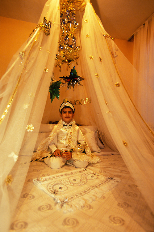 A newly circumcised boy poses for a portrait on his ceremonial bed in his home in Istanbul, Turkey. As local custom dictates, he is dressed up as a small sultan or prince and holds a sceptre in his hand.