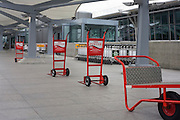 Skycap baggage trolleys line up awaiting business on the upper level in Departures at Heathrow airport's Terminal 5.