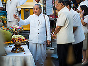 21 AUGUST 2015 - BANGKOK, THAILAND:  A Brahmin priest, left talks to Bangkok Governor SUKHUMBHAND PARIBATRA, right, at the Erawan Shrine Friday. The Bangkok Metropolitan Administration (BMA) held a religious ceremony Friday for the Ratchaprasong bomb victims. The ceremony started with a Brahmin blessing at Erawan Shrine, which was the target of a bombing Monday night. After the blessing people went across the street to the plaza in front of Central World mall for an interfaith religious service. Theravada Buddhists, Mahayana Buddhists, Muslims, Sikhs, Hindus, and Christians participated in the service. Life at the shrine, one of the busiest in Bangkok, is returning to normal. Friday the dancers and musicians who perform at the shrine resumed their schedules.        PHOTO BY JACK KURTZ