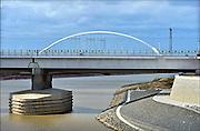 Nederland, Nijmegen, 15-9-2015De nevengeul aan de overkant van de Waal bij Lent nadert zijn voltooiing. Laatste werkzammheden. Grootste onderdeel van de vele werken van Rijkswaterstaat om bij hoogwater een betere waterafvoer in de rivier te hebben. Het is een omvangrijk project waarbij onder meer de pijlers van het spoorviaduct een bredere basis kregen omdat die straks in de loop van het water staan. Ook de n325 die vanaf de Waalbrug naar Arnhem loopt is over 400 meter opnieuw aangelegd omdat het talud vervangen wordt door een nieuwe brug met drie gracieuze pijlers. Het dorp veurlent komt op een kunstmatig eiland te liggen met twee bruggen als ontsluiting. Een voetgangersbrug en een andere, de Promenadebrug, voor normaal verkeer. Inmiddels begint de nieuwe kade aan de noordkant van deze geul vorm te krijgen. Ruimte voor de rivier, water, waal. In de nieuwe dijk wordt een drempel gebouwd die stapsgewijs water doorlaat en bij hoogwater overloopt.The Netherlands, NijmegenMeasures taken by Nijmegen to give the river Waal, Rhine, more space to flow during highwater and to prevent the risk of flooding. Room for the river. Reducing the level, waterlevel. Large project to create a new paralel gully, an extra flow of water, so the river can drain more water during highwater. Due to climate change and expected rise, increase of the sealevel, the Dutch continue to protect their land from the water.Foto: Flip Franssen/HH