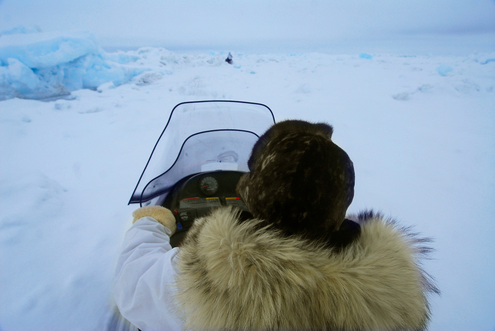 Alaska, Barrow. Cruising the ice of the frozen Arctic Ocen on a snow machine, going to the whaling camp. Spring whaling. (Model Release)